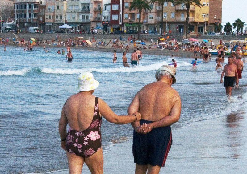 Una pareja de veraneantes ancianos pasean por la playa | Foto: M. Coheh bajo licencia Creative Commons