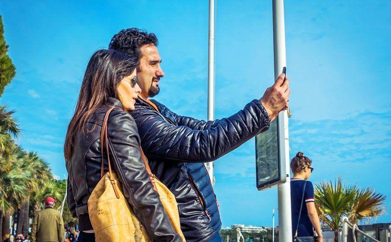 Dos turistas se realizan una foto frente a la playa | Foto: kpgolfpro para Pixabay