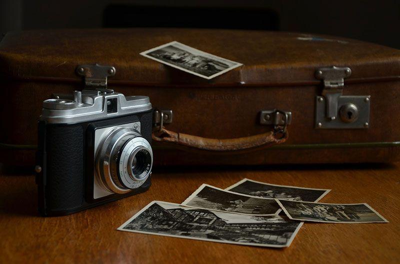 Cámara y fotografías desperdigadas junto a una maleta de viaje   Foto: Condesign para Pixabay