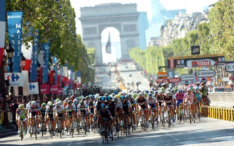 Participantes del Tour de Francia con el Arco del Triunfo de París al fondo